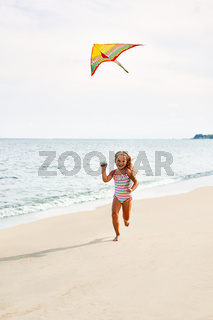Happy child girl with a kite running on tropical beach