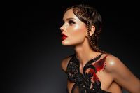 Beautiful young model with red lips and body art.