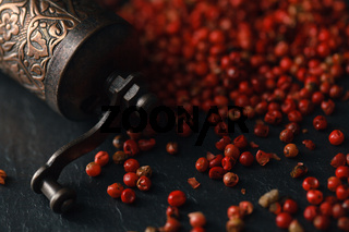 Organic Pink Peppercorn in wooden spoon on black slate stone background