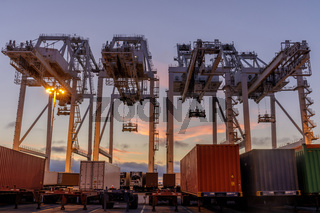 Shipping Container Cranes and Trucks with Sunset Sky in the Port of Oakland.