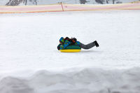 Snow tubing on ski resort at sunny winter day in mountains