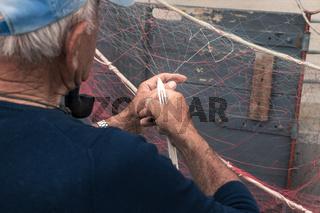 Fisherman repairs fishing net