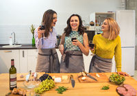 Female friends preparing a meal together and drinking red wine in the kitchen