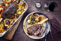 Venison knuckle with fried potatoes and vegetable as top view in a casserole and on a plate