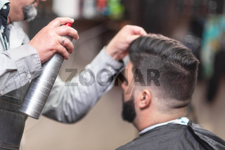 Master barber making modern hairstyle fixating hair with spray.