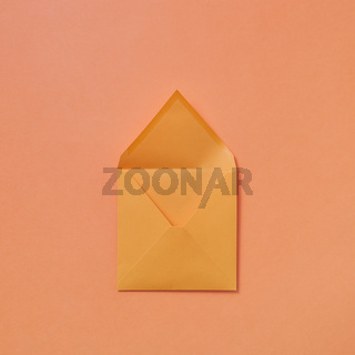 Handmade blank mock-up envelope on a peach color background.