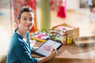 Fashion designer drawing a new model on a digital tablet