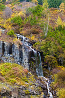 A waterfall on a hillside covered in colorful autumn trees and shrubs
