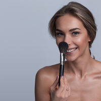 Woman holding makeup brush