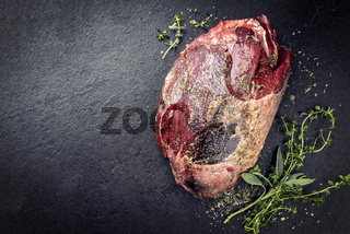 Raw dry aged haunch of venison as with herbs as close-up on a slate slab with copy space left