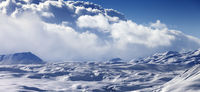 Panoramic view on snowy sunlight plateau and blue sky with clouds