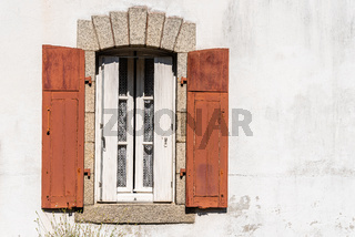 Old window with wooden red painted shutters