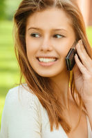 a beautiful young woman in a white dress speak on mobile phone