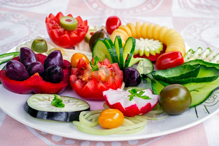 Plate of vegetarian breakfast food with cucumber, tomato, green olives, potato spiral, yellow cheese and red bell pepper on white silk tablecloth