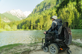 young man in a wheelchair fishing at the beautiful lake on a sunny day, with mountains in the back