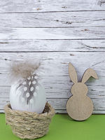 Easter background with Easter egg and Easter bunny isolated on green in front of wood