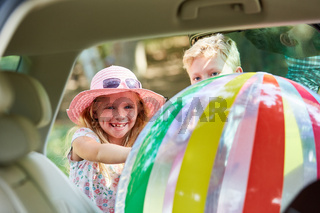 Kinder verstauen großen Ball im Auto