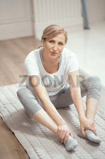 European Looking Woman Over 50 Years Old Doing Yoga at Home in the Living Room.