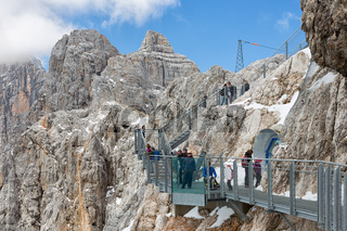 Austrian Dachstein Mountains with hikers passing a skywalk rope bridge