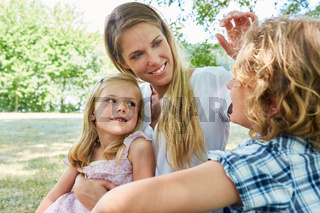 Glückliche Mutter mit zwei Kindern im Park