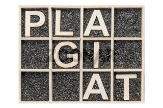 Word PLAGIAT on black sand