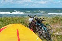 tourist tents on the seashore, cyclists on the seashore