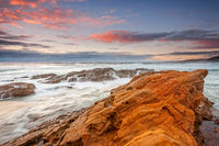 An emotional tempestuous ocean surges inland and cascades over rocks.