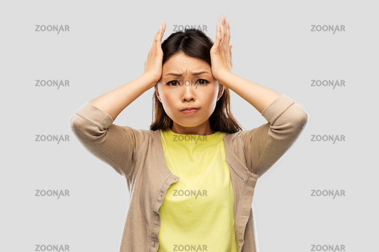 stressed asian woman holding to her head