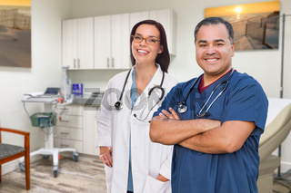 Hispanic Male and Caucasian Female Doctor Standing In Office