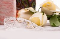Handiwork lace ribbon on the table among roses