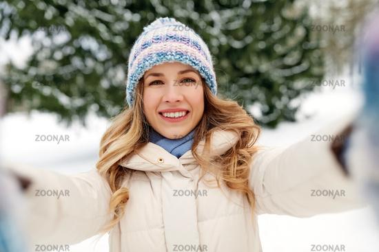 smiling woman taking selfie outdoors in winter