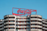 The Coca Cola logo advertising neon light letters on building roof in Berlin
