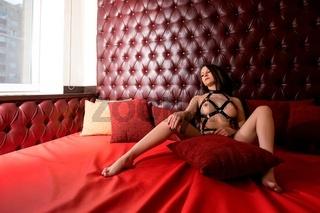 Pretty brunette in bdsm underwear on a sofa view
