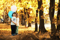 Little children are walking in autumn park