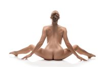 Nude woman sitting in a split isolated view
