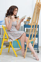 woman with easel, palette and brush painting at art studio