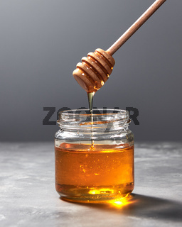 Fragrant organic fresh honey dripping from wooden stick to a glass pot on a gray marble table, pure natural sweet goodness.