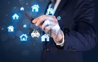 Businessman holding keys with houses around