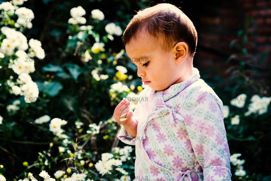 Baby playing with white flowers in garden