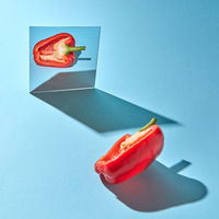 Half a ripe pepper is reflected in a mirror on a blue background with copy space and shadows. Healthy vegetable