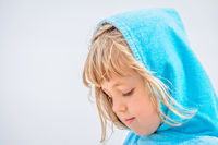 Girl with head covered in a blue towel