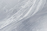 Snowy off piste slope with traces of skis and snowboards