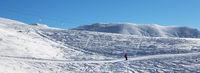 Skier downhill on ski slope at sun morning
