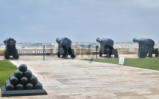 Four heavy Guns and saluting battery in the upper barrakka gardens. In the foreground a pyramid of cannonballs.