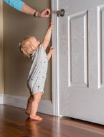 Young baby just able to walk reaching up for the door handle on wooden floor