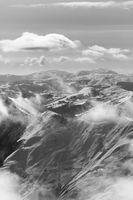 Black and white snowy sunlight mountains in haze and cloudy sky