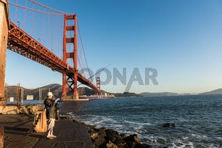 SAN FRANCISCO, USA – OCTOBER 12, 2018: Fisherman with the Golden Gate Bridge in the background at Fort Point