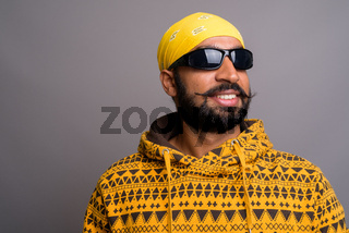 Young handsome Indian man wearing hoodie while thinking