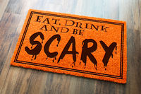 Eat, Drink and Be Scary Halloween Orange Welcome Mat On Wood Floor Background