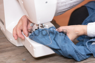 Close-up of senior woman hands seamstress sewing jeans on electrical sewing machine.
